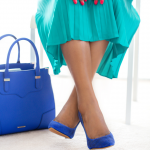 Successful woman sitting with her legs crossed and a blue handbag, wearing blue high heals.