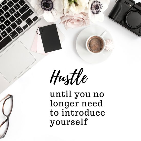 Quote Hustle until you no longer need to introduce yourself written on a woman's desk, with her laptop, camera, and a cup of coffee