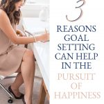 Successful Business Woman at her desk writing goals with the words 3 reasons goal setting can help in the pursuit of happiness