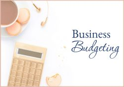 womans desktop with macaroons, calculator and earbuds in rose gold business budgeting bootcamp business course