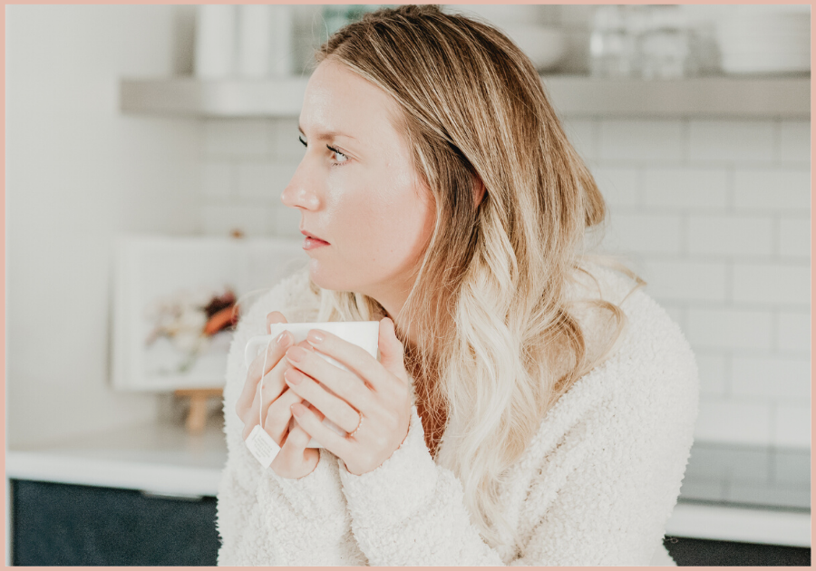 woman holding a tea cup in her kitchen, gazing off to her right. Business training, business burnout