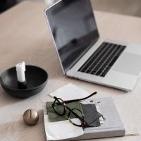 Get into the entrepreneurial mindset with laptop, candle, note book and glasses on a desk