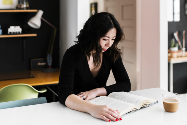Woman reading a book at her kitchen table, thank you for becoming an insider