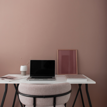 Laptop on desk beside a dusty rose wall